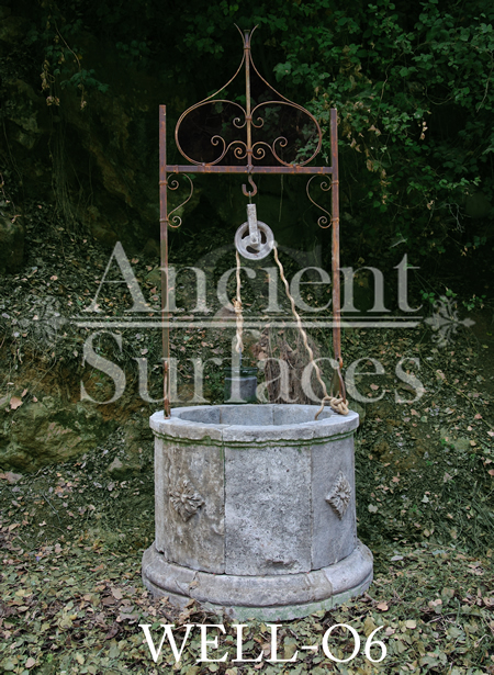 Anceint reclaimed limestone well with rosette motifs on its 4 faces salvaged from Italy topped with old hand twisted metal work