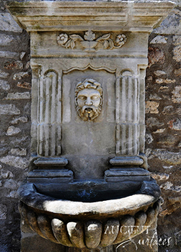 Antique stone wall fountain salvaged from the island of Corsica