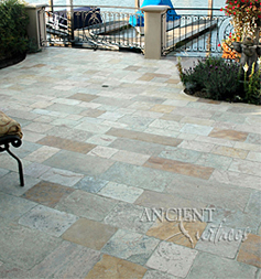 The 'Arcane stone' are ancient reclaimed limestone flooring tiles from the 17th century and later. Pavers in this photo are shown installed on a pool deck overlooking the bay in coastal Californian town