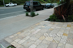 Ancient Reclaimed 'Arcane Stone' pavers salvaged from 17th century era homes, villas and farmhouses from sleepy southern European towns and villages. In this picture this limestone is shown installed on a driveway and in the garage of this coastal Mediterranean home. The Arcane Stone is perfect for all types of external and internal weather conditions and traffic volumes.