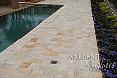 The 'Arcane stone' are ancient reclaimed limestone flooring tiles from the 17th century and later. Pavers in this photo are shown installed on a pool deck